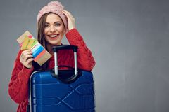 Happy woman with toothy smile holding credit card, passport and. Tickets for travel. Gray wall back Stock Photos