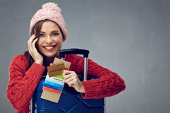Happy woman with toothy smile holding credit card, passport and. Tickets for travel. Gray wall back Royalty Free Stock Photography