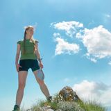Happy woman on the top of a mountain. With blue sky and clouds Stock Image