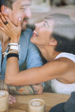 Happy woman touching the cheek of man in cafe Stock Photos