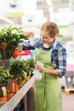 Happy woman touching mandarin tree in greenhouse Stock Photo