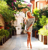 Happy woman tourist on background of blooming street Royalty Free Stock Image