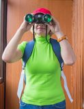 Happy woman tourist with backpack looking through binoculars, search purpose, gathering information, outdoor activity. Concept Stock Images