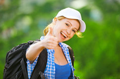 Happy woman tourist with a backpack shows thumb up Royalty Free Stock Images