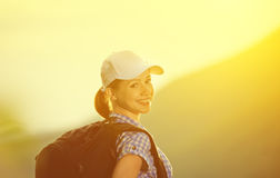 Happy woman tourist with a backpack  on sunset Stock Image
