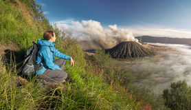Happy woman tourist with backpacker enjoying sunrise view at hi. Beatiful view of the sunrise over the valley with the volcanoes of Java island. Indonesia royalty free stock images