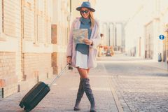 Happy woman tourist with exploring map and luggage while standin Royalty Free Stock Photo