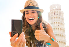 Happy woman tourist giving thumbs up taking selfie in Pisa. A smiling, laughing woman tourist is taking a selfie at the Leaning Tower of Pisa, giving a happy Royalty Free Stock Photography