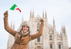Happy woman tourist with Italian flag rejoicing near Duomo Stock Image