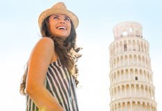 Happy woman tourist at Leaning Tower of Pisa. A happy female tourist is smiling, looking back over her shoulder. In the distance, the Leaning Tower of Pisa Stock Photography