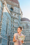 Happy woman tourist with map looking on something near Duomo Stock Photography