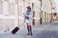 Happy woman tourist  with  map and luggage while standing in the. Happy woman tourist  with exploring map and luggage while standing in the street, trendy woman Stock Images