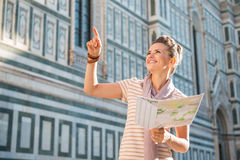 Happy woman tourist with map pointing on something near Duomo Stock Image