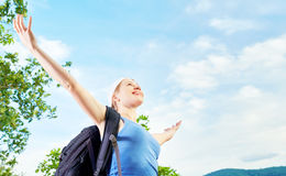 Happy woman tourist opened his hands on top of the mountain agai Stock Photo