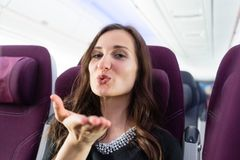 Happy woman tourist with pleasant anticipation on airplane. Happy woman passenger with pleasant anticipation on airplane stock image