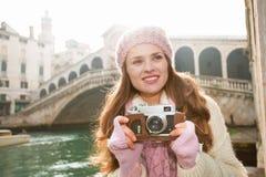 Happy woman tourist with retro photo camera near Rialto Bridge Stock Photo