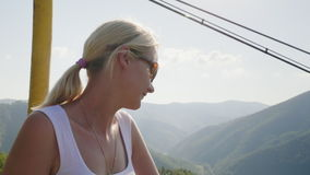 A happy woman tourist is riding at the ski lift in the summer. Holidays in the mountains in the summer season stock video footage