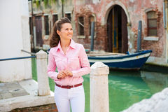 Happy woman tourist standing by Venice canal, looking upwards Stock Image