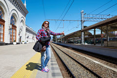 Happy woman tourist thumbs up on railroad station Stock Images