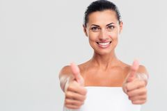 Happy woman in towel showing thumb up sign stock images