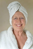 Happy woman with towel wrapped around her head. Royalty Free Stock Images