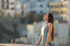 Happy woman in a town breathing fresh air. From a rural apartment balcony stock photography