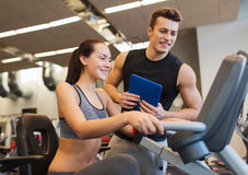 Happy woman with trainer on exercise bike in gym Royalty Free Stock Image