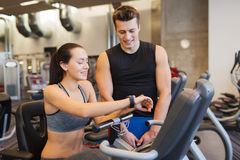 Happy woman with trainer on exercise bike in gym Stock Photos