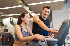 Happy woman with trainer on exercise bike in gym Stock Photography