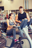 Happy woman with trainer on exercise bike in gym Stock Images