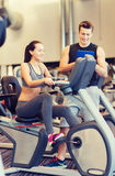 Happy woman with trainer on exercise bike in gym Royalty Free Stock Photography