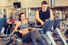 Happy woman with trainer on exercise bike in gym Royalty Free Stock Photos