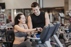 Happy woman with trainer on exercise bike in gym Royalty Free Stock Images