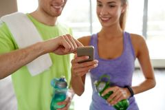 Happy woman and trainer showing smartphone in gym Royalty Free Stock Images