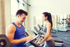 Happy woman with trainer on treadmill in gym Royalty Free Stock Photos