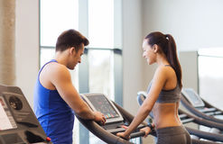 Happy woman with trainer on treadmill in gym Stock Image