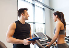 Happy woman with trainer on treadmill in gym Royalty Free Stock Photo