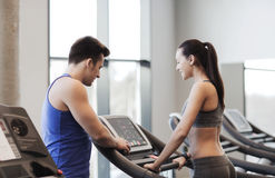 Happy woman with trainer on treadmill in gym Stock Photography