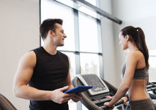 Happy woman with trainer on treadmill in gym Royalty Free Stock Image