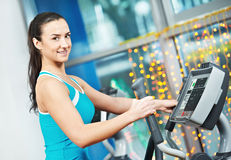 Happy woman with at training gym. Woman with training equipmant at fitness club gym doing exercises for back muscles Stock Image