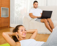 Happy woman training on mat and inert boyfriend resting Royalty Free Stock Photography