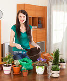 Happy woman transplanting potted flowers Royalty Free Stock Images