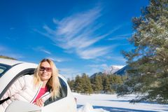 Happy woman travel by car in winter stock photography