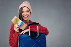 Happy woman with travel case holding passport, ticket and credit. Card. Isolated on gray wall back Royalty Free Stock Photo