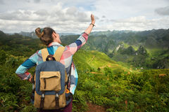 Happy woman traveler with backpack enjoying a beautiful view of Stock Images