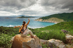 Happy Woman traveler looking on the edge of the bay. Stock Image