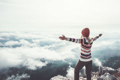 Happy woman traveler on mountain summit hands raised royalty free stock photo