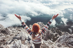Happy woman traveler on mountain summit hands raised up stock image