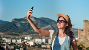 Happy woman traveler posing at mountain landscape taking selfie using smartphone. Medium close-up. Smiling active backpacker female having fun in amazing stock footage