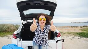 Happy woman traveler with suitcases near her car. A young girl traveler with suitcases stands near her car stock video footage